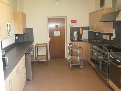 a kitchen with 3 overs, plenty of cupboards and shelving